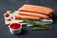 Raw Frankfurter Sausages With Ketchup On Cutting Board.