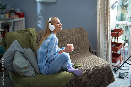 Attractive young lady with hot drink listening music at home - 242556817
