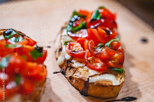 Fotografía  Traditional Italian bruschetta with cherry tomatoes, cheese, basil and balsamic vinegar on wooden board