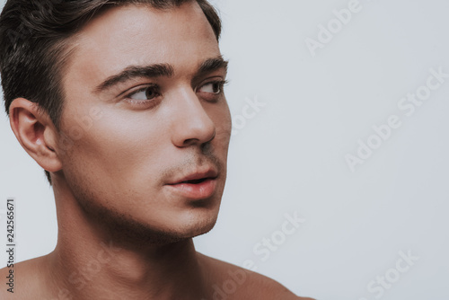 Fotografie, Tablou  Portrait of curious young man looking aside