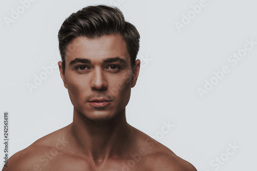 Fotografia, Obraz  Close up of dark haired man standing against the grey background