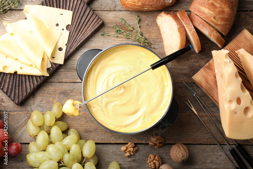 Photo  Flat lay composition with pot of delicious cheese fondue on wooden table
