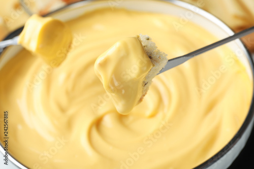 Piece of bread over pot with delicious cheese fondue, closeup