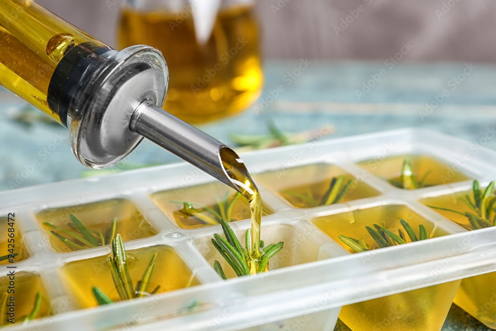 Fototapety, obrazy: Pouring olive oil into ice cube tray with rosemary on table, closeup