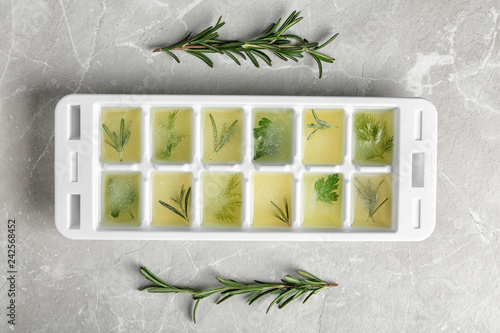 Ice cube tray with herbs frozen in oil and fresh rosemary on grey background, flat lay