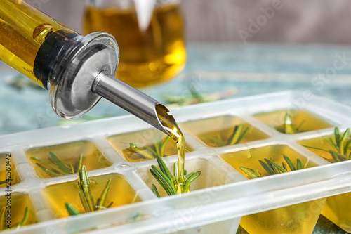 Spoed Fotobehang Aromatische Pouring olive oil into ice cube tray with rosemary on table, closeup