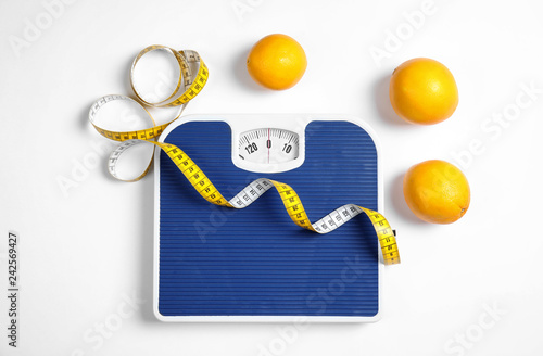 Fotografie, Obraz  Composition with scales, oranges and tape measure on white background, top view