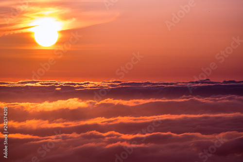 Poster Crimson Bright sunlight reflected on a sea of clouds before sunset