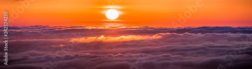 Poster Crimson Panoramic view of a fiery sunset over a sea of clouds covering San Francisco bay area, California