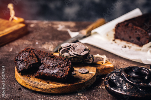 Fotografie, Obraz  Arrangement of sweet chocolate bread cake with chips on wooden board on rough ta
