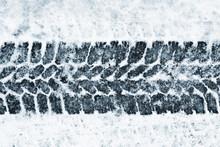 Black Tyre Mark Shape On Snowy Frozen Blue Road Background.