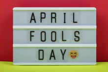 April Fool's Day Lettering On Lightbox On Red And Yellow Background.