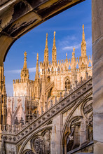 Vertical: Sunset Exterior Rooftop View Fo Duomo Di Milano With Spires, Blue Sky, And Architectural Details