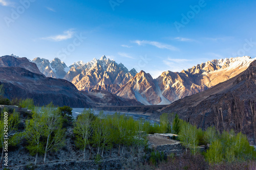 Keuken foto achterwand Asia land Tupopdan mountain also known as Passu Cones or Passu Cathedral, big rocks all over the place and blue crystal of Hunza river at sunset time ,Northern of Pakistan