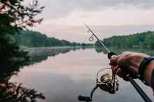 Fisherman With Fishing Rod, Spinning Reel On The Background River Bank. Sunrise. Fog Against The Backdrop Of Lake. Misty Morning. Wild Nature. The Concept Of Rural Getaway. Article About Fishing Day.