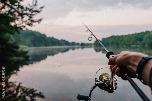 Carta da parati Fisherman with fishing rod, spinning reel on the background river bank