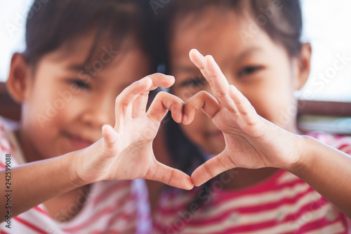Foto  Two cute asian child girls making heart shape with hands together with love
