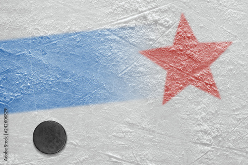 Photo  An image of a blue line with a red star on ice and a hockey puck
