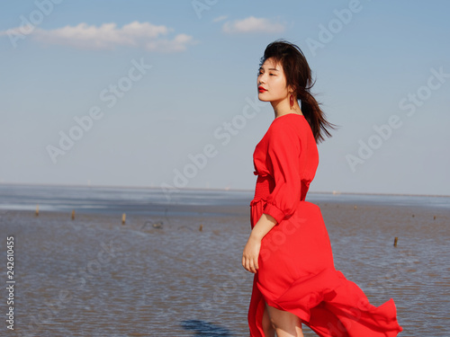 8f35ef9ad197 Sexy Chinese young girl in red dress posing on sunny beach with eyes closed  like dreaming