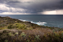 Long Exposure Shot Of Oceanside Meadow And Ocean Shore With Downpouring Storm At London Bridge Lookout In Portsea, Australia