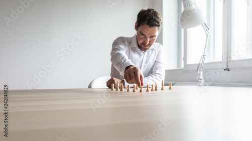 Fotografie, Obraz  Young business executive positioning white chess pieces in a sensible structure