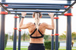 Leinwanddruck Bild - Rear view of slim girl blonde powerlifter doing pull ups on horizontal bar showing strong muscles during sports activities on street sports grounds. Bodybuilding concept and beautiful physical shape