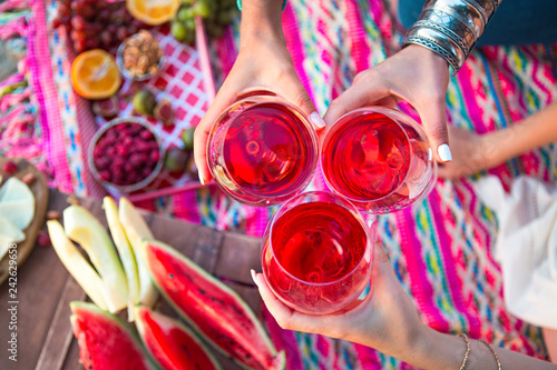 Outdoor picnic with rose wine, fruits, nuts meat and cheese