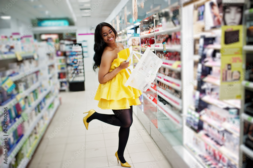 Fototapety, obrazy: Stylish african american woman at yellow dreess posed at cosmetic store, buying with basket make up accessories on beauty shop.