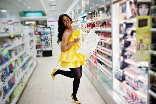Obraz Stylish african american woman at yellow dreess posed at cosmetic store, buying with basket make up accessories on beauty shop. - fototapety do salonu
