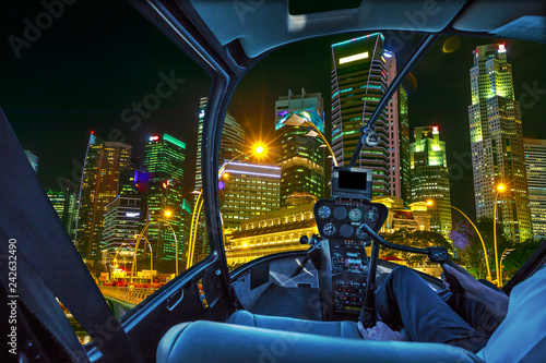 Staande foto Aziatische Plekken Helicopter interior on Singapore financial buildings and skyscrapers of downtown reflected in the sea of the harbor. Scenic flight above Singapore skyline by night in marina bay promenade waterfront.