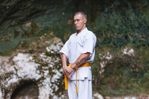 Fotografía  Focused strong-willed adult male sportsmen in a white suit for martial arts conc