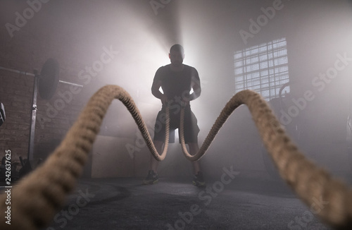 Obraz na plátne Silhouette of man working out with battle ropes at gym.
