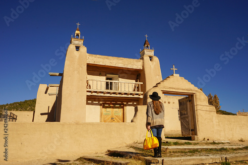 Fotografie, Obraz  A lady standing in front of a church in New Mexico, travel