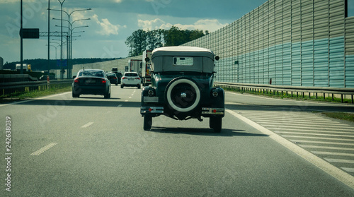 Cadres-photo bureau Vintage voitures Old model vintage car driving on the highway with modern cars.