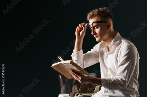 Obraz na plátně Book writer wearing glasses and white shirt sitting on the table with typewriter