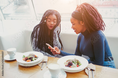 Two african american women sit in cafe at table. They look at phone. Food in balls are on table.