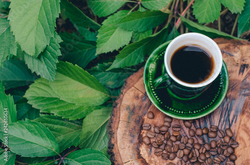 Foto op Aluminium Cafe A cup of coffee on a cut tree with coffee beans and leaves.