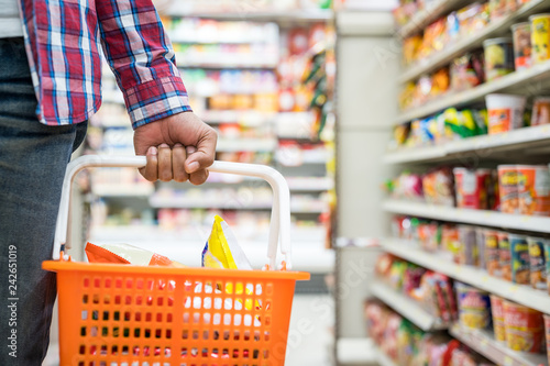 Fotografía  Men's hand holding basket in the supermarket, Grocery shopping concept
