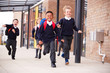 Happy primary school kids, wearing school uniforms and backpacks, running on a walkway outside their school building, front view, close up