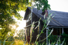Old Wooden Abandoned Building In Nature, Against A Background Of Sunset And Vegetation