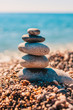 Smooth large sea pebbles are stacked on the seashore - Zen Concept
