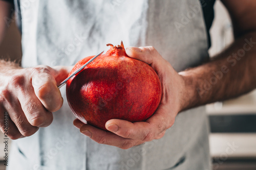 A man with strong hands cuts a pomegranate with a knife - close-up - 242655830