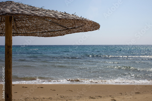Fotografiet  Closeup View of Woven Thatched Roof Umbrella Standing alone on the Beachfront