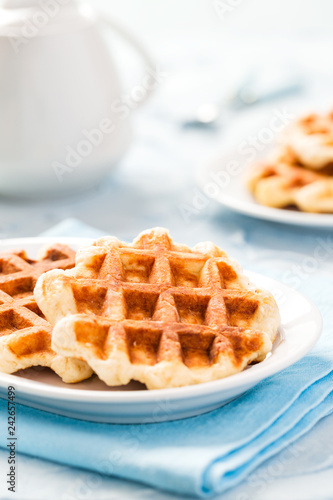 Fotografía  Belgian waffles with white teapot on pastel blue background for breakfast concept