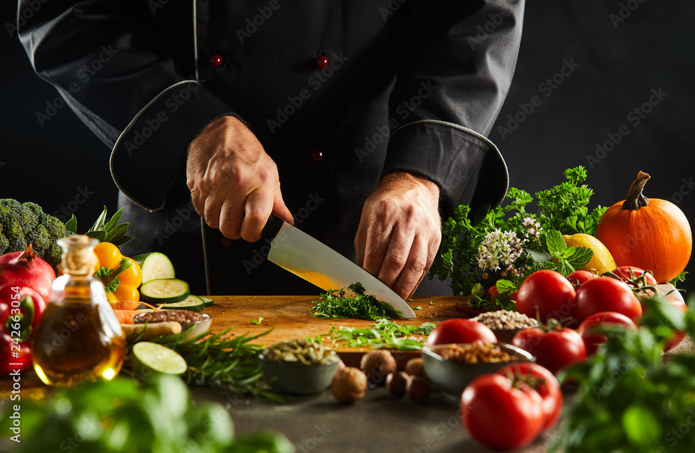 Fototapety, obrazy: Chef dicing fresh herbs with a kitchen knife