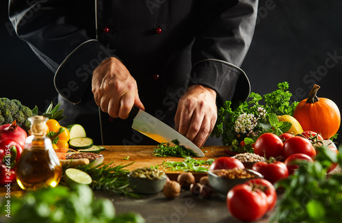Fotografie, Obraz  Chef dicing fresh herbs with a kitchen knife