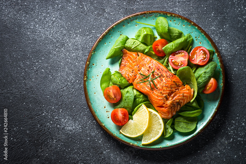 Fotografia Baked salmon fish fillet with fresh salad top view.