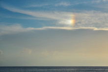 Blue Cloudy Sky With Rainbow Effect Over The Sea On A Sunset As A Natural Background.