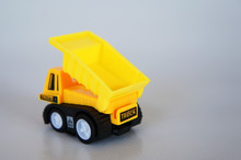 Selective Focused On Yellow Toy Dump Truck Made From Plastic. Isolated On White Background.