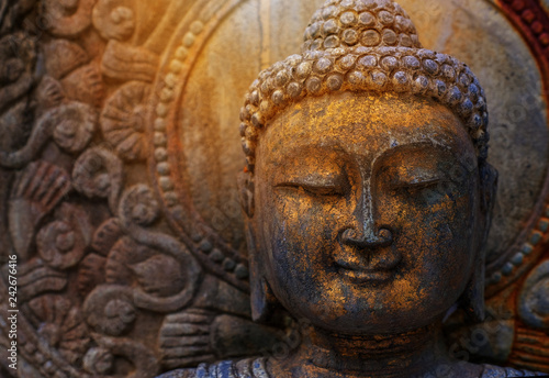 Fotografia Rock Buddha statue with sunlight used for amulets of Buddhism religion